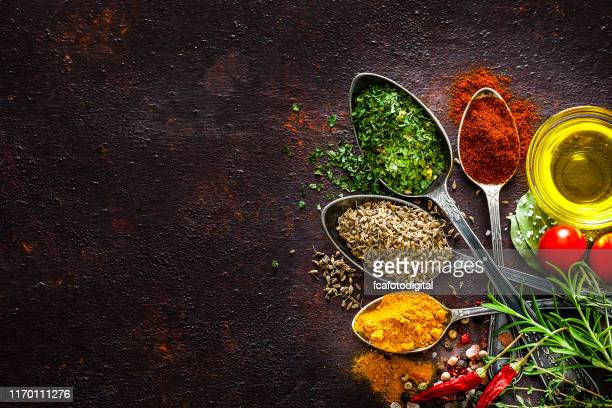 cooking and seasoning backgrounds: spices and herbs in vintage spoons shot from above on rustic brown table - indian food stock pictures, royalty-free photos & images