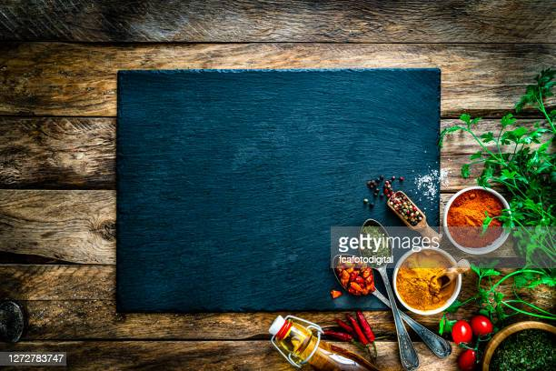 cooking background: multi colored spices, herbs and vegetables on rustic wooden table. copy space - chopping board stock pictures, royalty-free photos & images