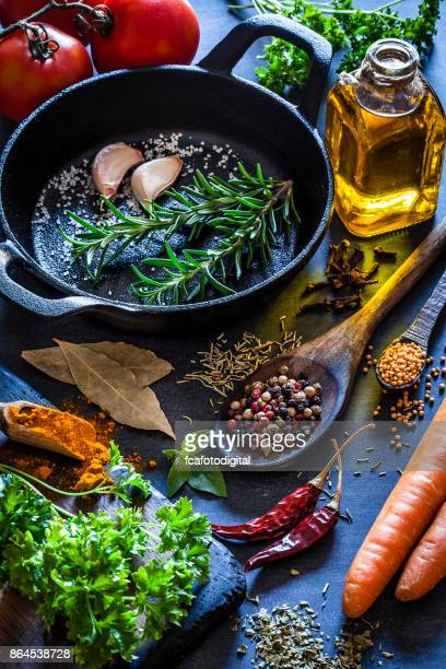 Cooking: black cast iron pan with spices and herbs on dark kitchen table