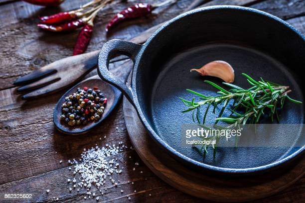 Cooking: black cast iron pan with spices and herbs on wooden kitchen table