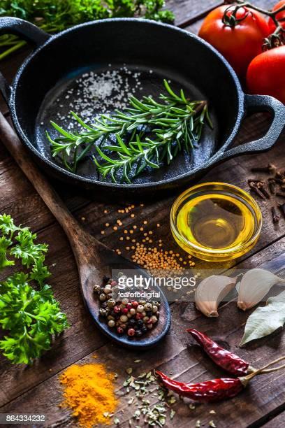 Kochen: schwarze Gusseisen Pfanne mit Gewürzen und Kräutern auf Holz Küchentisch