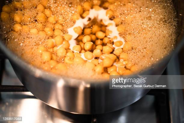 cooking / boiling the soaked chickpeas in a stainless steel saucepan - vegetarian food stock pictures, royalty-free photos & images
