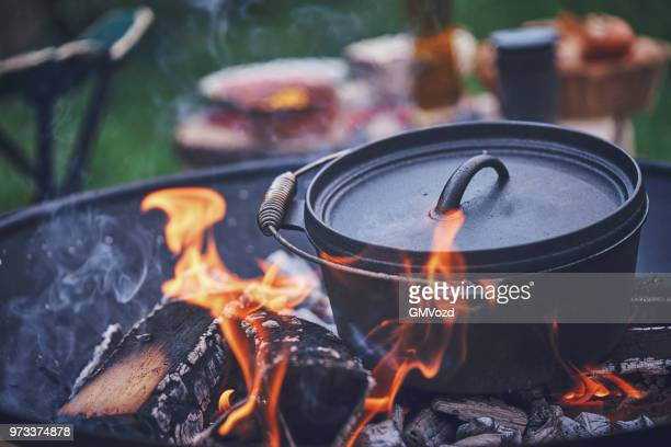 cooking chili con carne in dutch oven over logfire - warming up stock pictures, royalty-free photos & images