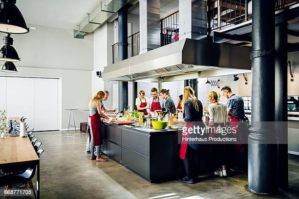 Cooking class in working in modern kitchen