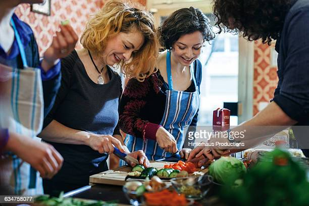 cooking class participants enjoy cutting vegetable - zusammenhalt stock-fotos und bilder