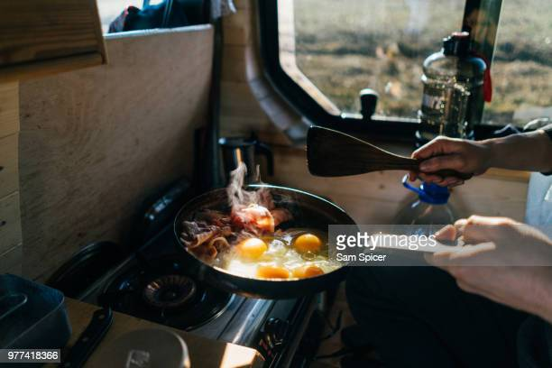 cooking eggs and bacon in skillet at campsite - sunday stock pictures, royalty-free photos & images
