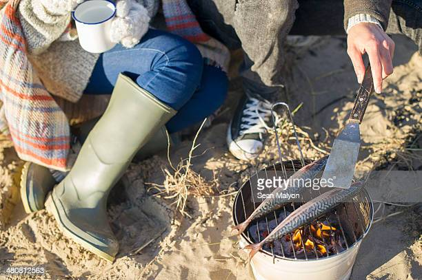 cooking fish on the beach - sean malyon stock pictures, royalty-free photos & images