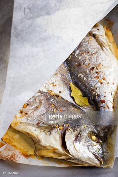 cooking fish paper - dorado fish stock photos and pictures