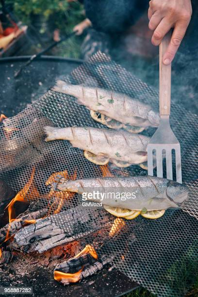 Cooking Fish with Lemon Over Open Campfire