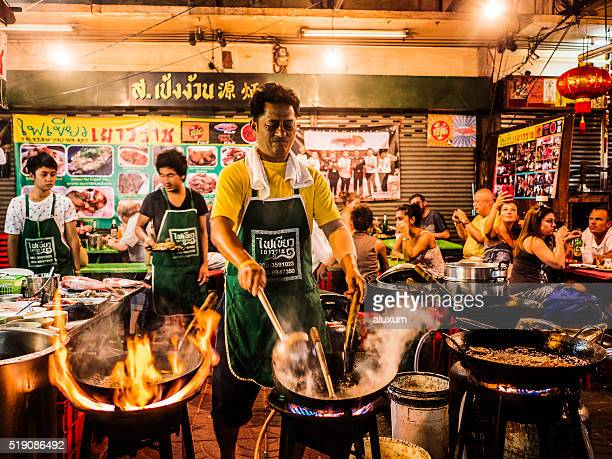 cooking food in the street chinatown bangkok thailand - bangkok stock photos and pictures