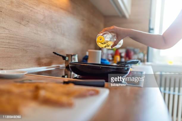 cozinhando o alimento, derramando o oi da azeitona. - frito - fotografias e filmes do acervo