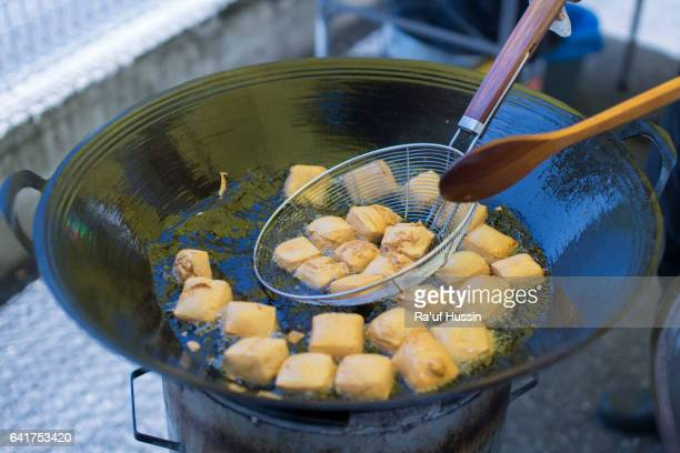Cooking frying tofu in pan with boiling oil