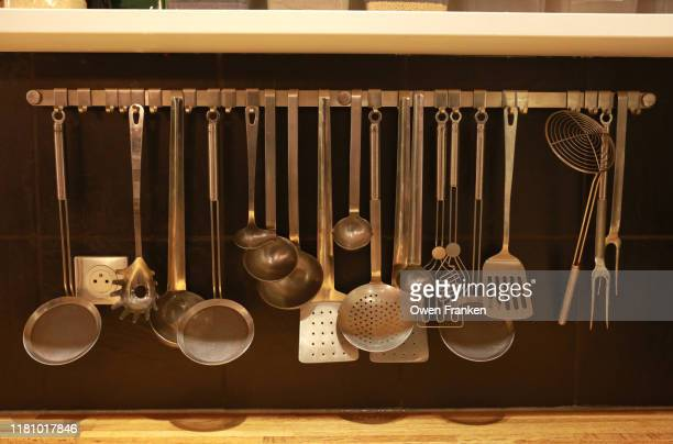 cooking instruments hanging in a professional kitchen - image photos et images de collection