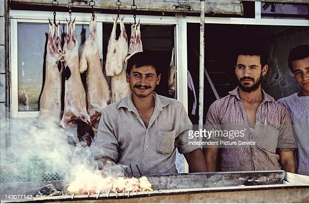 Cooking kebobs in front of a butcher shop in Amman Jordan