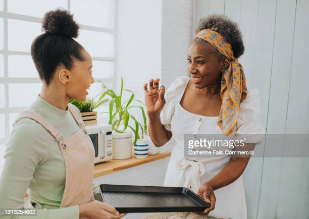 cooking lesson - woman explaining a cooking method to a student - mother stock pictures, royalty-free photos & images