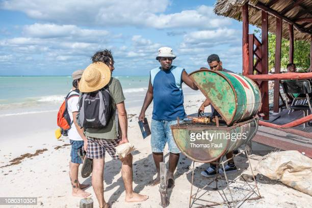 Cooking lobster on a oil drum BBQ on the beach in Cuba