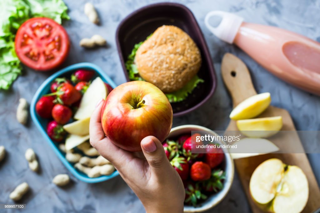 Cooking lunch for the child to school. On the gray kitchen table. Sandwich, strawberries and peanuts in lunchboxes. Top view. Woman holding an apple : Stock Photo