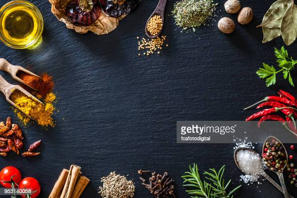Cooking nd seasoning spices border on black slate background