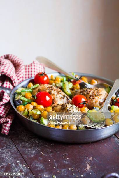 cooking pan with roasted chicken legs or drumsticks, chickpea, zucchini, cherry tomatoes on a wooden table, selective focus. image with copy space. - コース料理 ストックフォトと画像