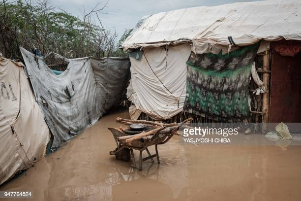 Cooking pot rests on top of a stove on a wheelbarrow beside flooded shelters after a heavy rainy season downpour at the Dadaab refugee complex, in...