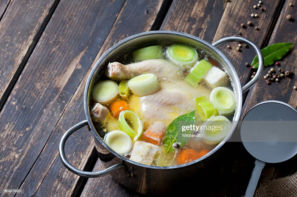 Cooking pot with raw corn-fed chicken, onion, herbs and greens : Stock Photo