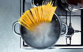 Cooking raw spaghetti in the boiling water contained in a saucepan