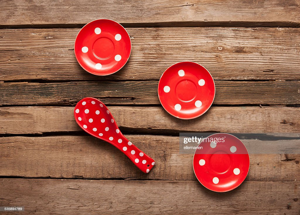 cooking red spoon and plates with polka dots, wooden background : Bildbanksbilder