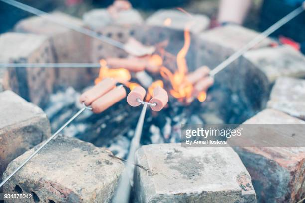 Cooking sausages on campfire