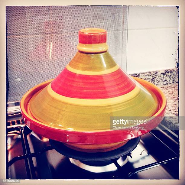 cooking tajine on gas stove at home - moroccan culture stock photos and pictures