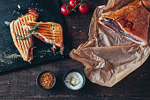cooking tasty panini with ham covered with cheese, tomatoes
