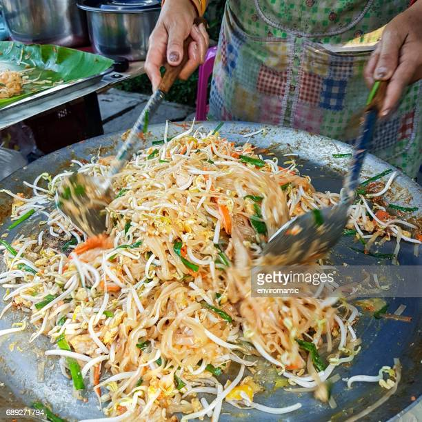 cooking the famous thai street food dish called 'pad thai', which is a stir fried dish of noodles, bean sprouts, vegetables with chicken or prawns, wrapped in a thin omlette. - thai food stock pictures, royalty-free photos & images