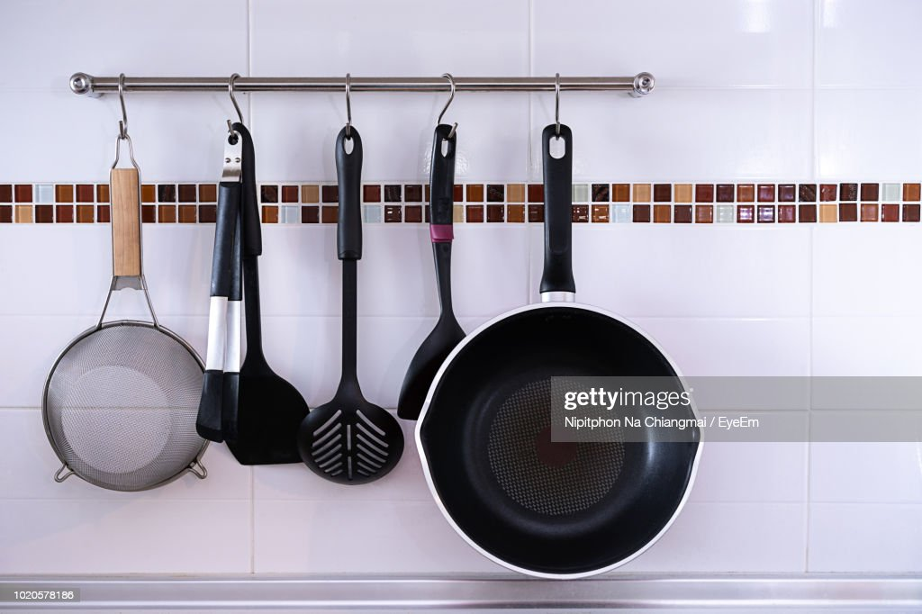 Cooking Utensils Hanging On Rack Tiled Wall Stock Photo