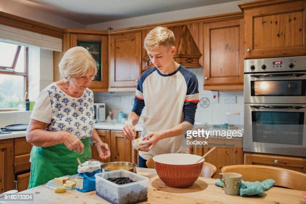 cooking with her grandson - british granny stock photos and pictures
