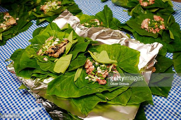 Cooking with taro leaves and tined fish, Taianas beach resort.