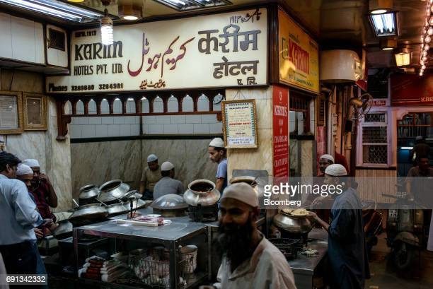 Cooks and waiters prepare and serve food at a restaurant outside the Jama Masjid at night during the Muslim holy month of Ramadan in the Old Delhi...