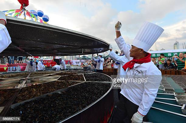 Cooks cover the large cauldron where 24 kinds of seafood will be cooked during the 8th Qingdao International Sailing Week Qingdao International...