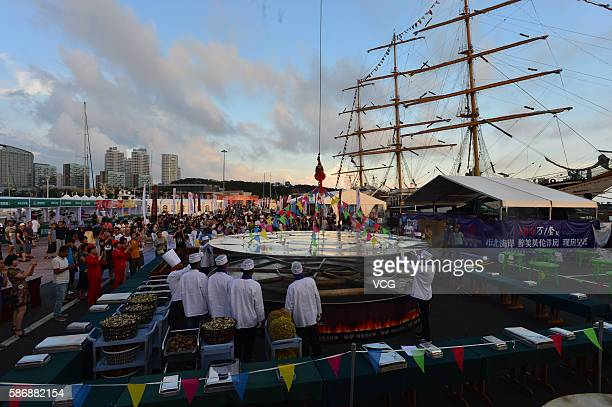 Cooks handle the large cauldron where 24 kinds of seafood will be cooked during the 8th Qingdao International Sailing Week Qingdao International...