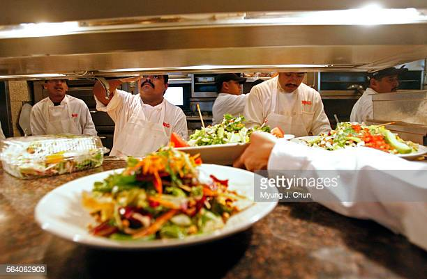Cooks hustle to feed the lunchtime crowd at the Cheesecake Factory in Sherman Oaks on Friday July 28 2006 High gas prices have caused people to spend...