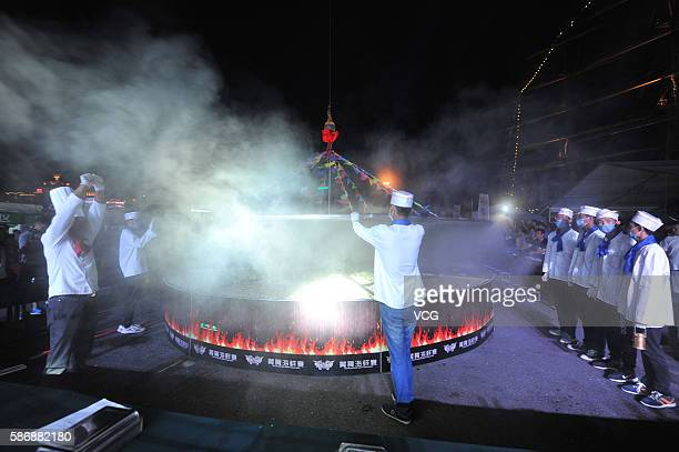 Cooks lift the lid of a large cauldron where 24 kinds of seafood are cooked during the 8th Qingdao International Sailing Week Qingdao International...