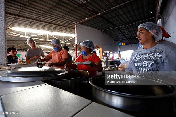 Cooks prepare food for those affected by the spill of molasses in the El Hurtado dam in the community of San Pedro Valencia that resulted in the...