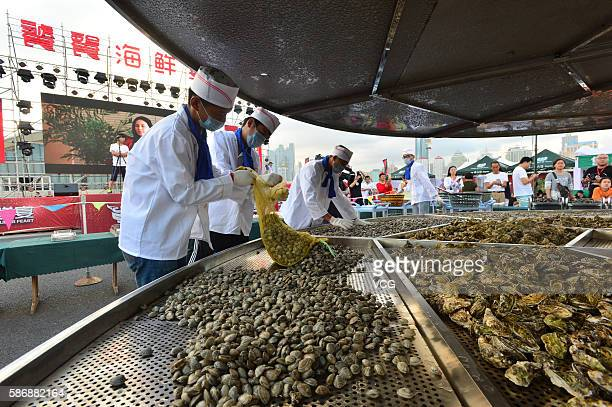 Cooks prepare the large cauldron where 24 kinds of seafood will be cooked during the 8th Qingdao International Sailing Week Qingdao International...