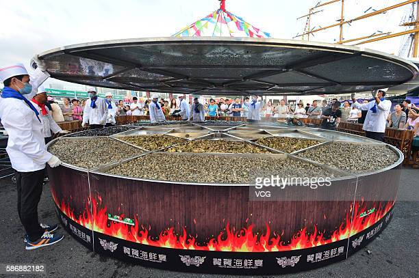 Cooks prepare to cover the large cauldron where 24 kinds of seafood will be cooked during the 8th Qingdao International Sailing Week Qingdao...