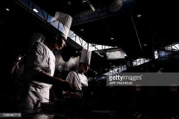 Cooks work in a booth of the SIRHA International Hostel, Restaurant and Food fair in Eurexpo hall in Chassieu, near Lyon, central eastern France, on...