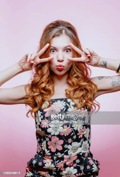cool 60's looking woman making a face and peace sign - gogo danseuse photos et images de collection
