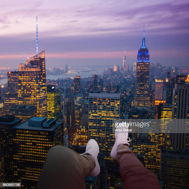 Cool aerial view from helicopter of guy with white shoes and legs from personal perspective over the view of Manhattan cityscape at dusk with purple colors in the sky.