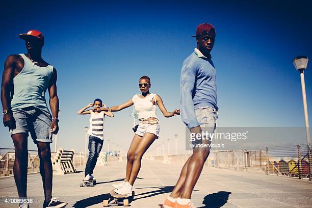 Coole African American Teenager longboarding am Strand
