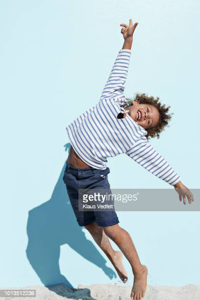 cool and cute boy jumping on beach with backdrop - somente crianças - fotografias e filmes do acervo