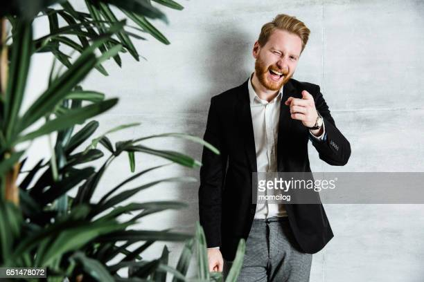 Cool and handsome businessman pointing at you