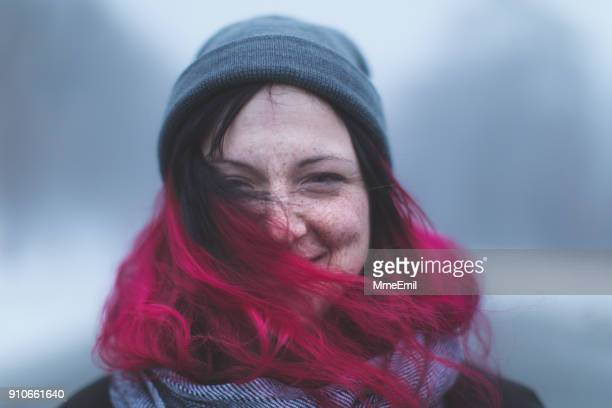 cool and smiling young woman standing on a rural road by a foggy winter day in canada - dyed red hair stock pictures, royalty-free photos & images