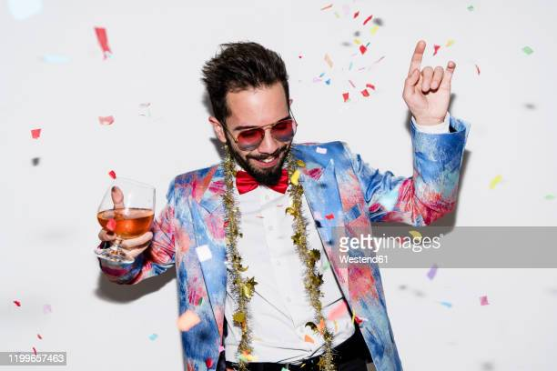 cool and stylish man wearing a colorful suit and sunglasses dancing at a party - multi colored suit stock pictures, royalty-free photos & images